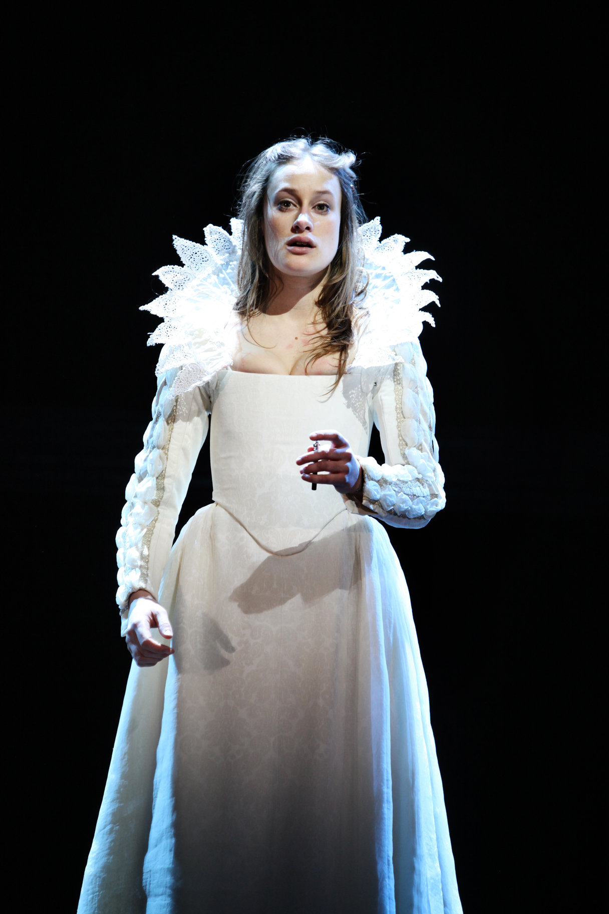 Juliet in an elaborate white gown prepares to drink the poison