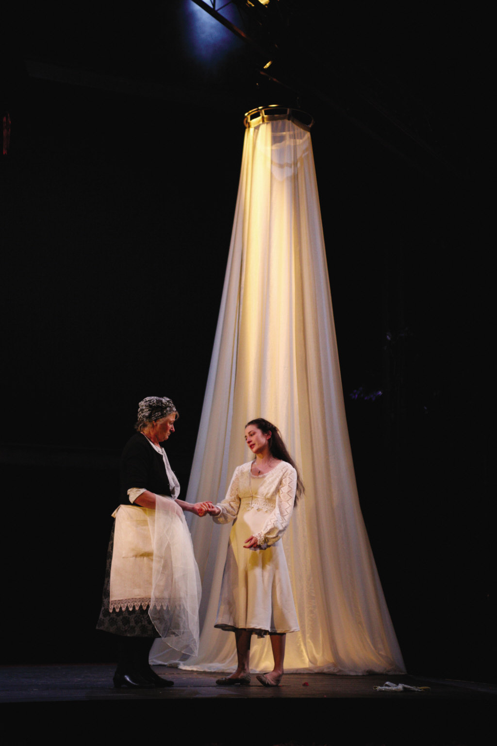 The Nurse and Juliet hold hands in front of a white canopy.