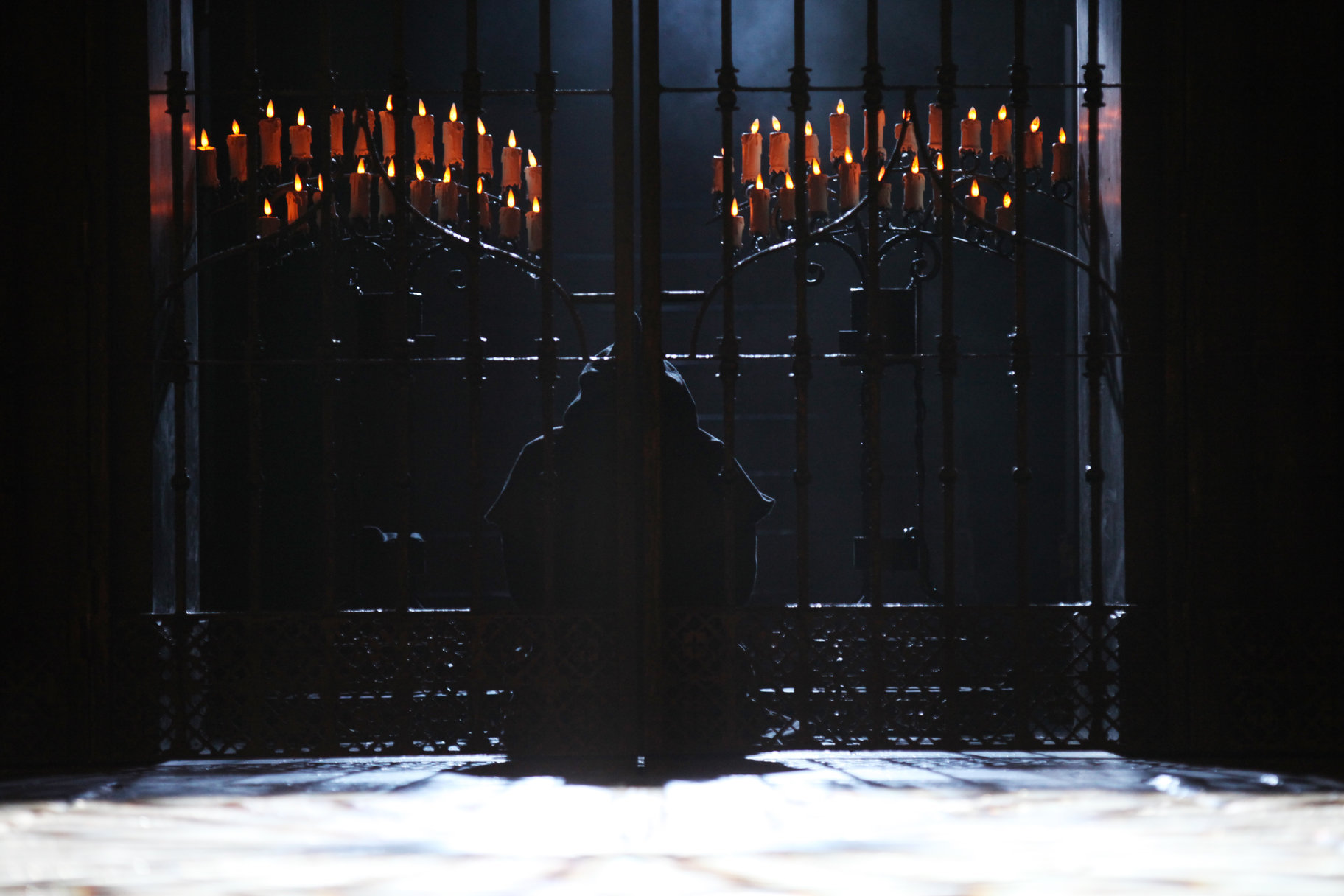 A dark figure stands behind an iron gate lit with two rows of red candles.