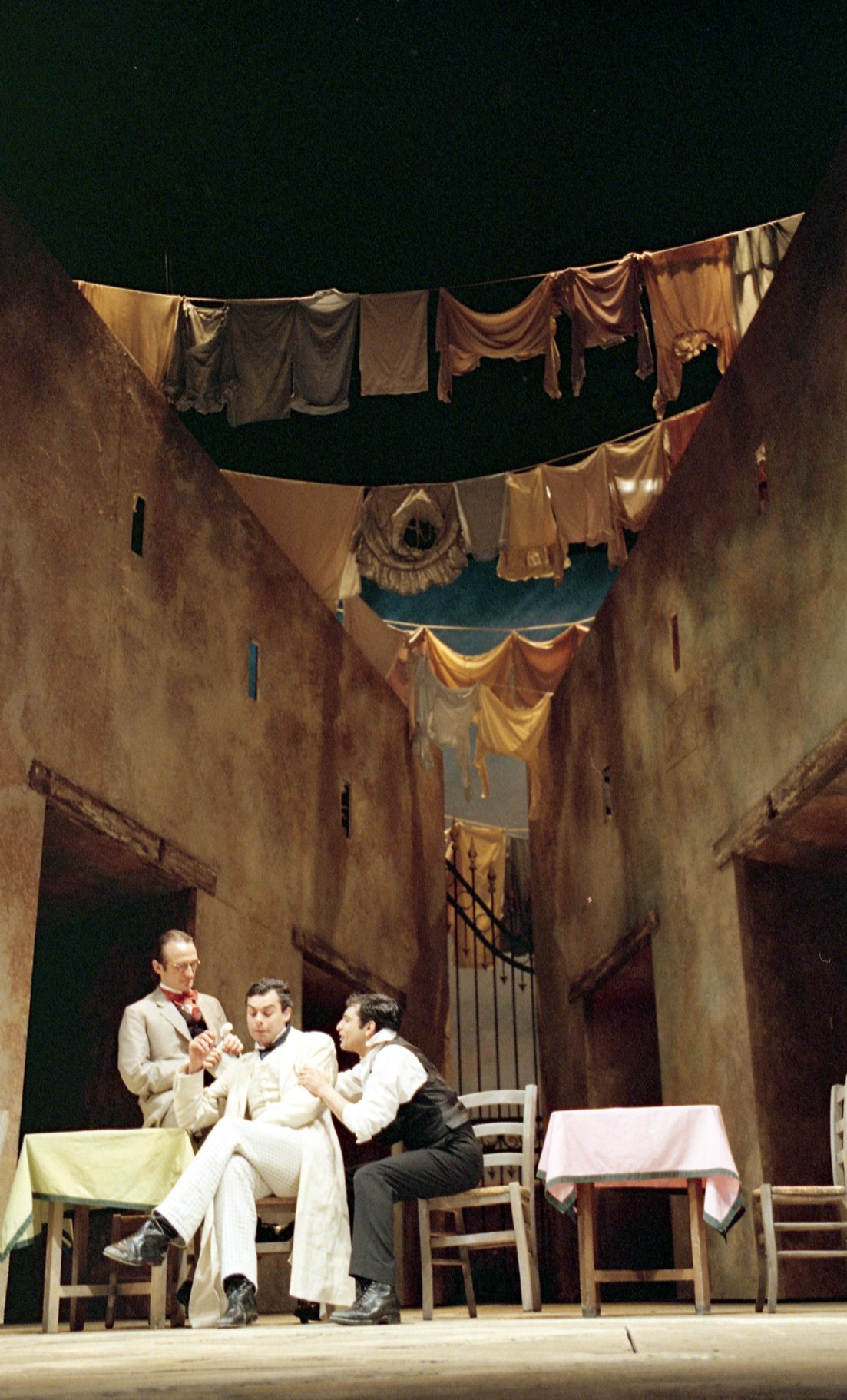Benvolio, Mercutio and Romeo sit in an alleyway on stage with washing hanging over the head.