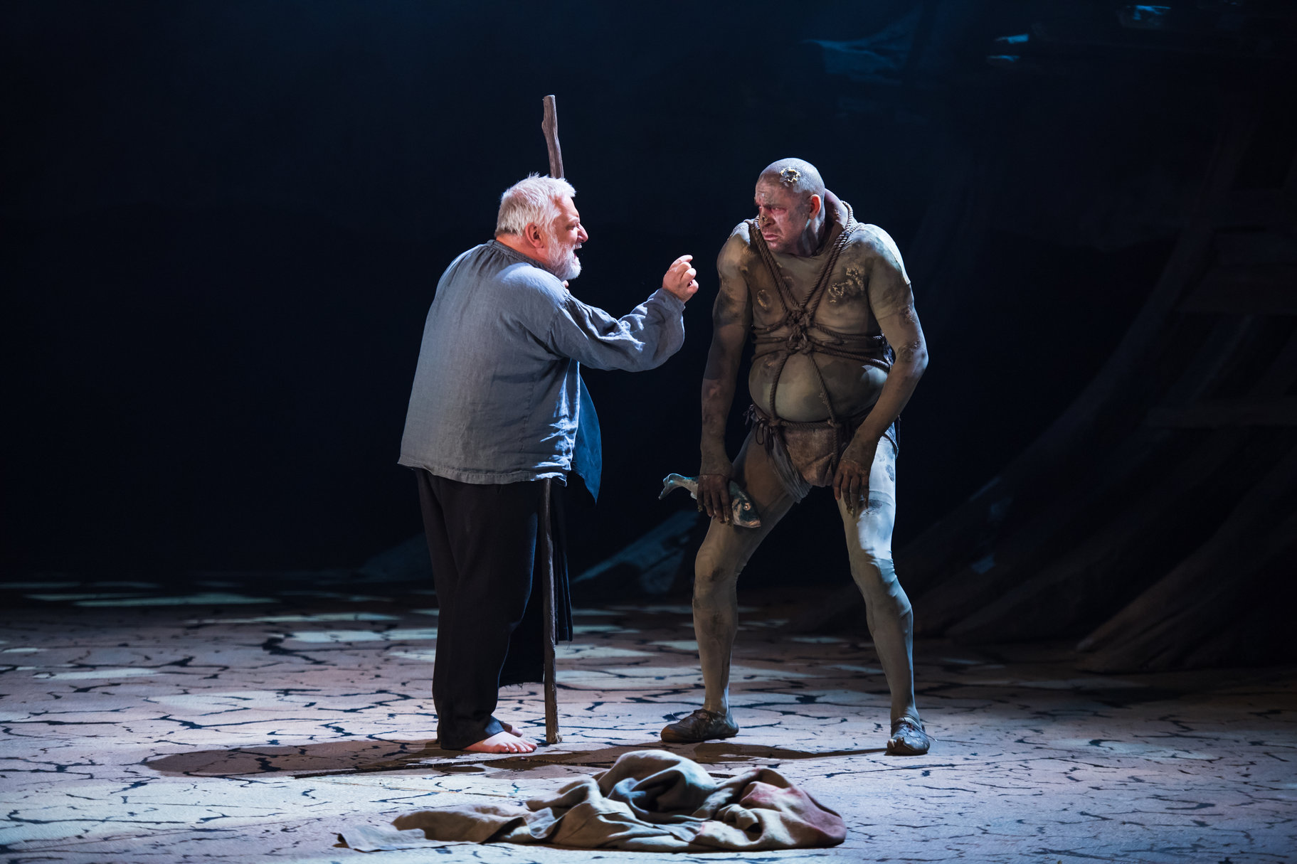 Prospero talks to a cowering Caliban.