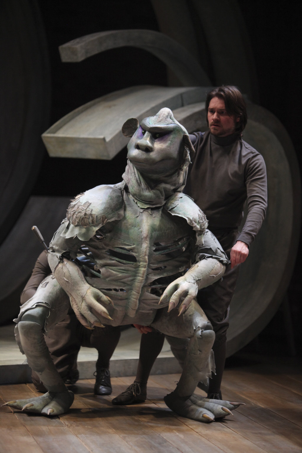 A man works a puppet of Caliban.