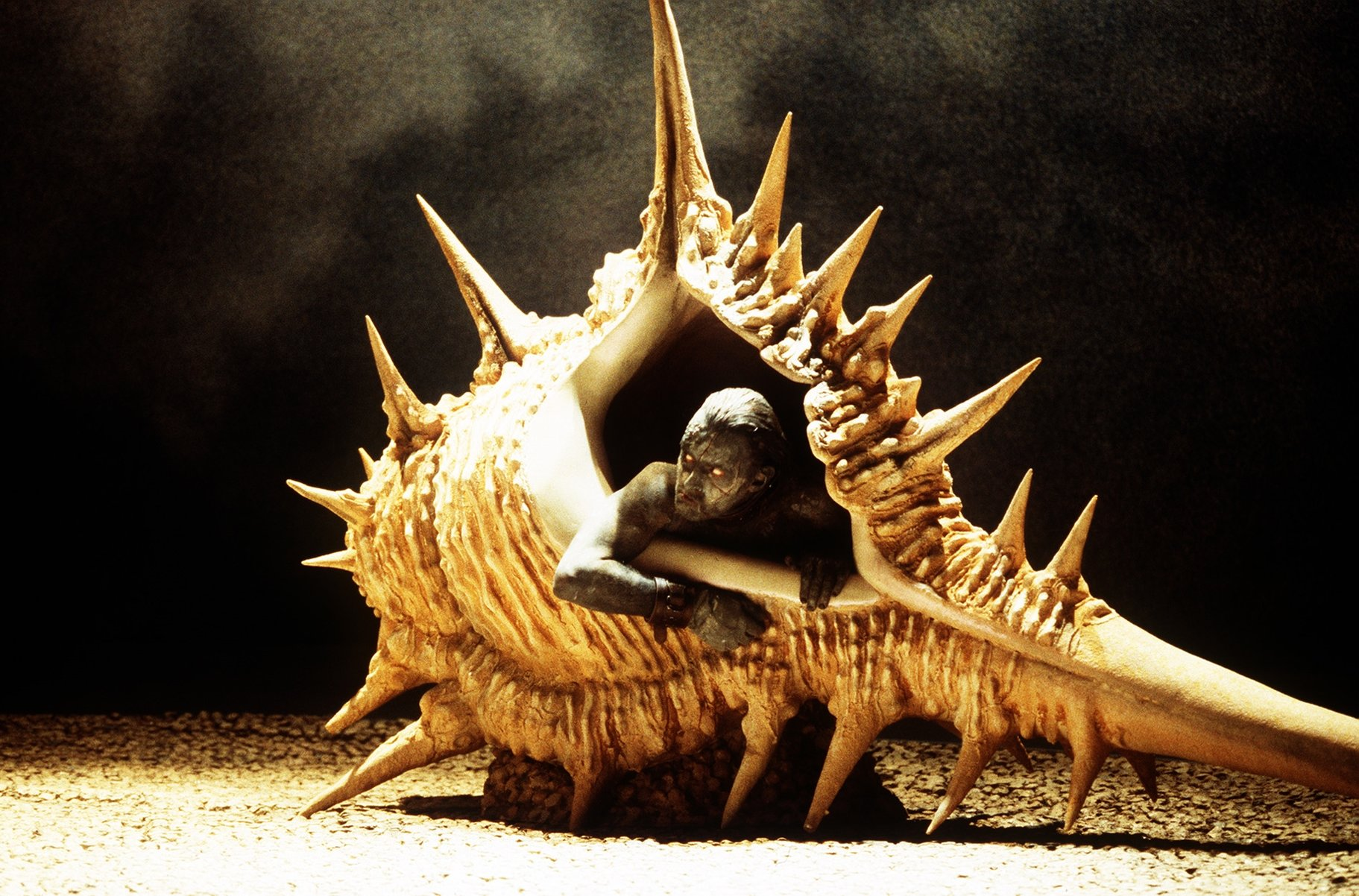 Robert Glenister as Caliban, sitting in a large shell.