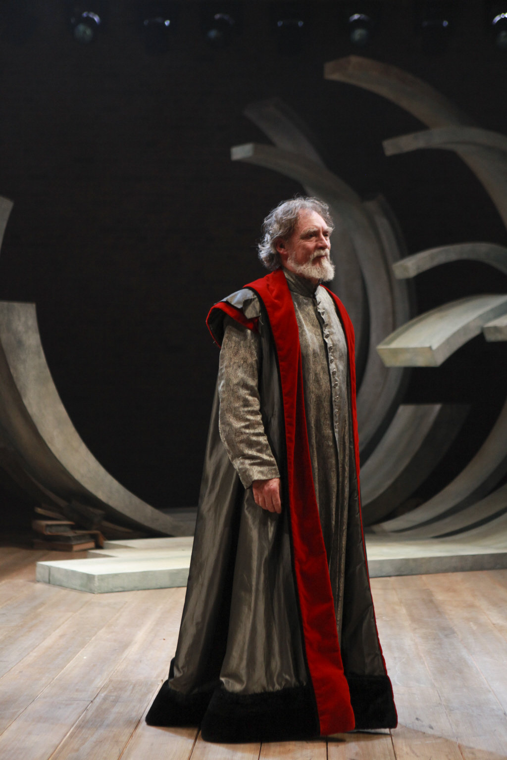 Prospero in a long robe with red trimmings.
