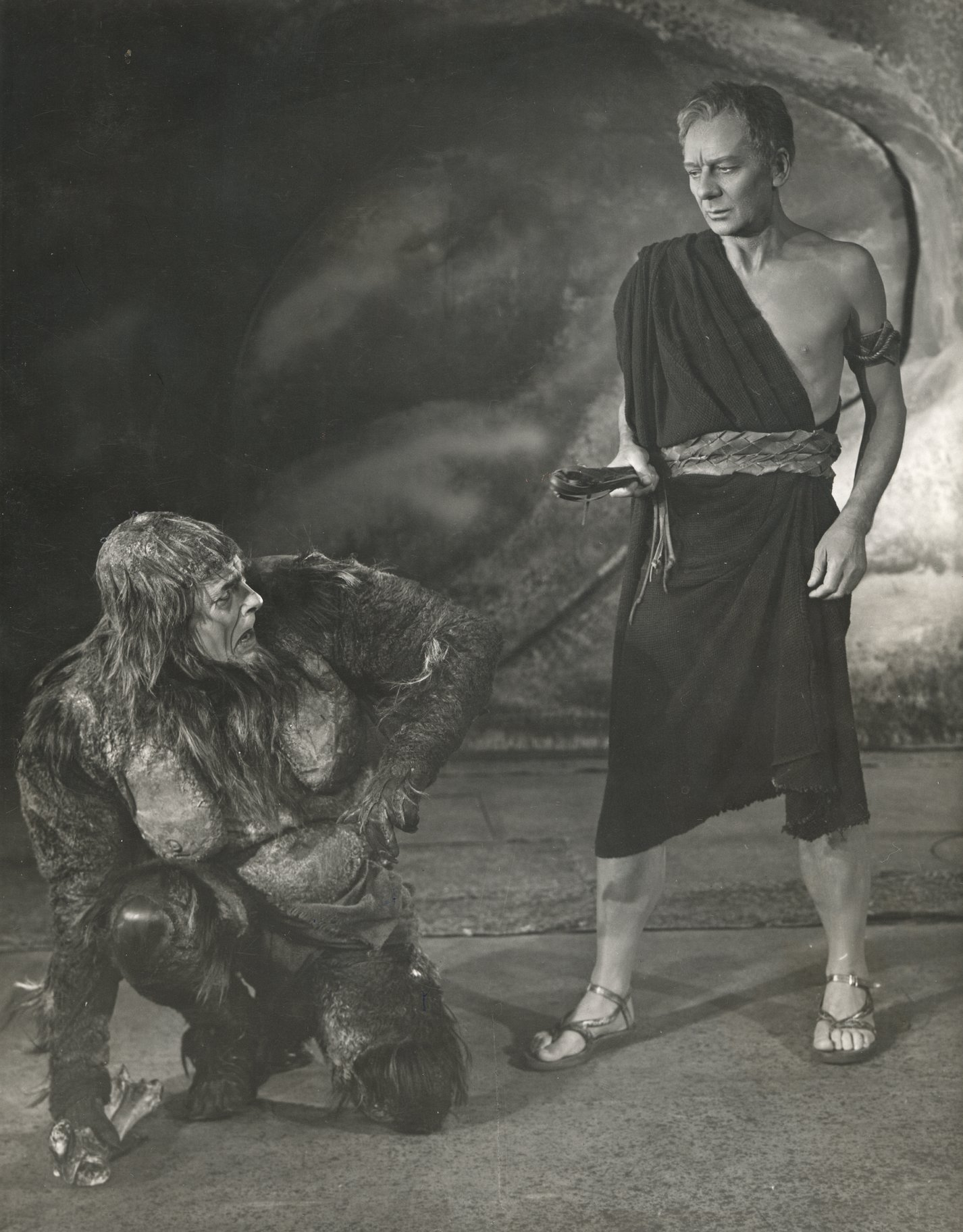 Caliban crouches next to Prospero.