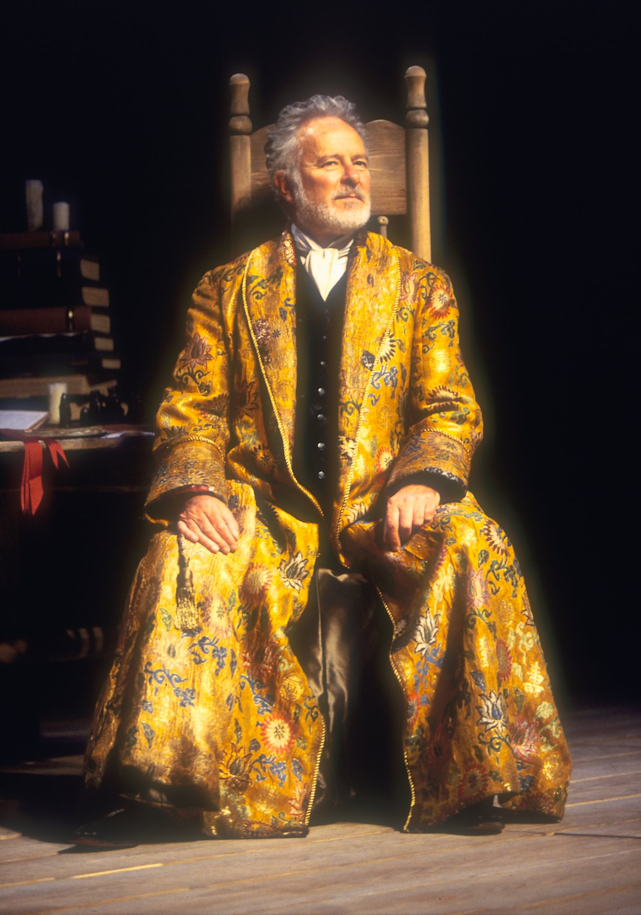 Prospero sits in a chair, wearing an intricate golden robe.