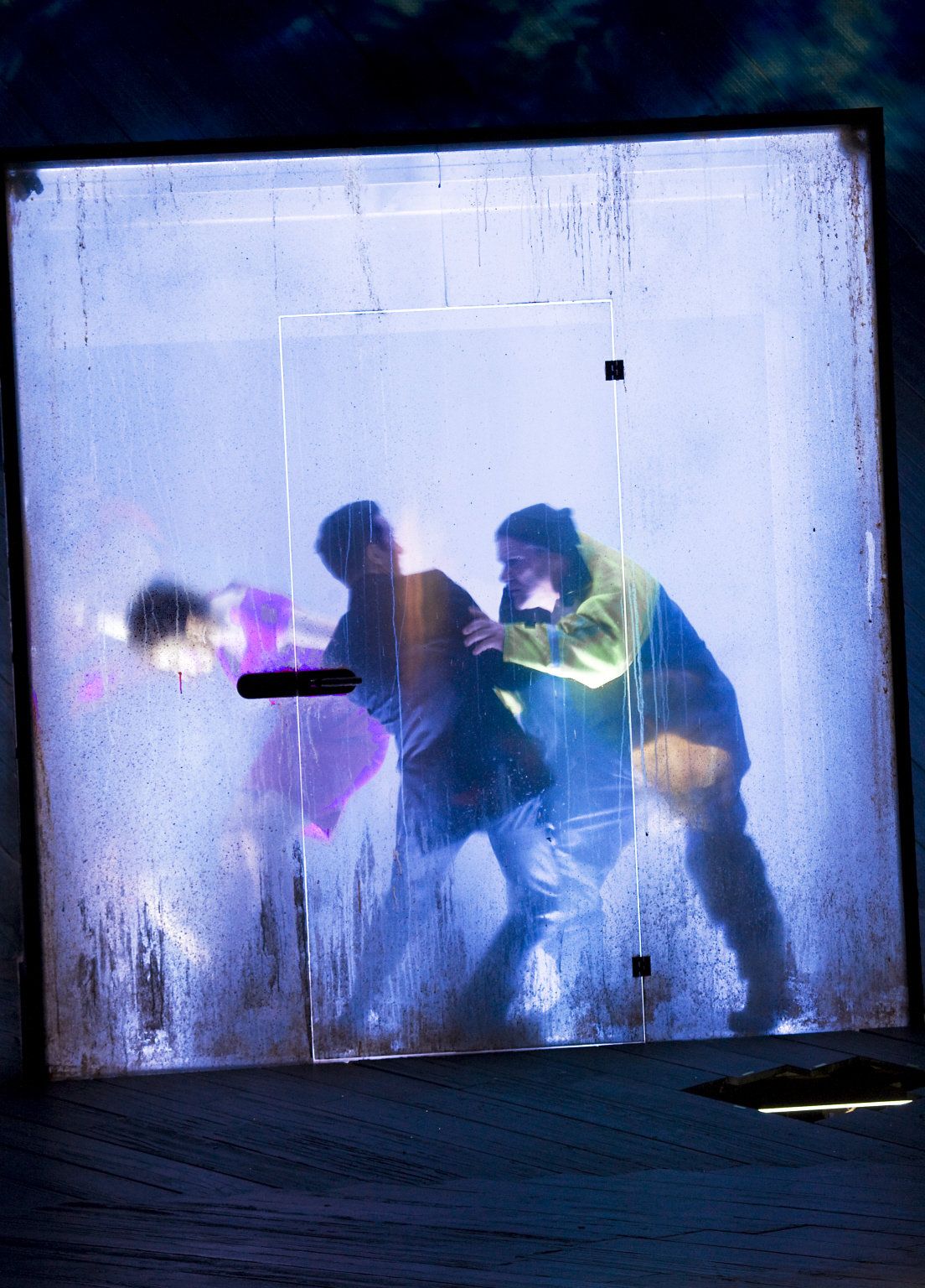 Three people in a see-through box, representing the boat in the storm.