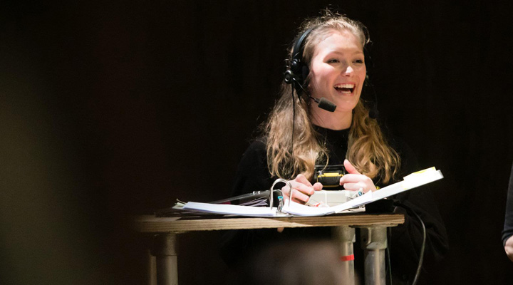 young woman on a dark background wearing a headset laughing