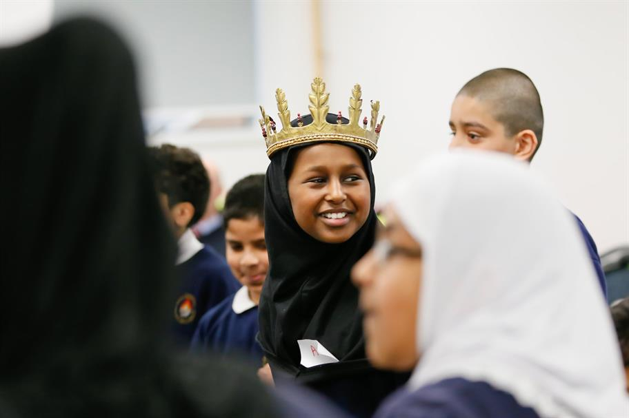 A young person in school uniform wears a golden crown and is surrounded by her classmates