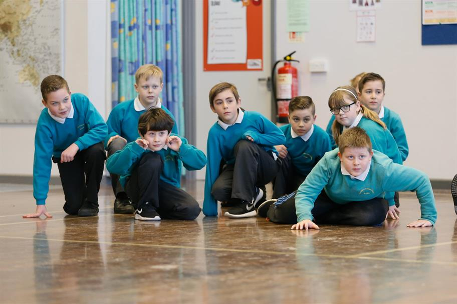 a group of children in teal school uniform jumpers crouching down on the floor acting