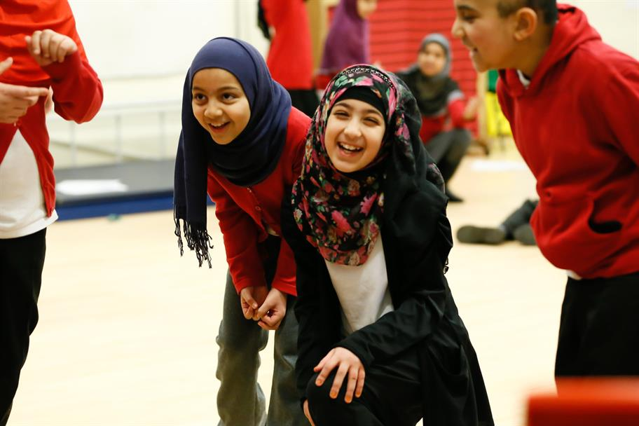 Two young girls in school uniform and headscarves giggling together in a school hall