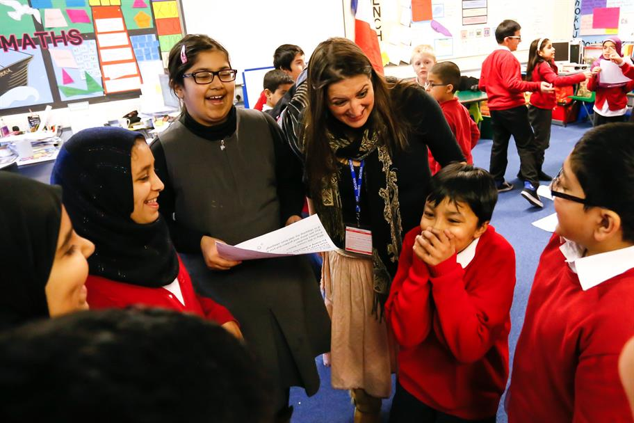 A schoolchild in a red uniform covers his mouth as he laughs, surrounded by other smiling students and a teacher