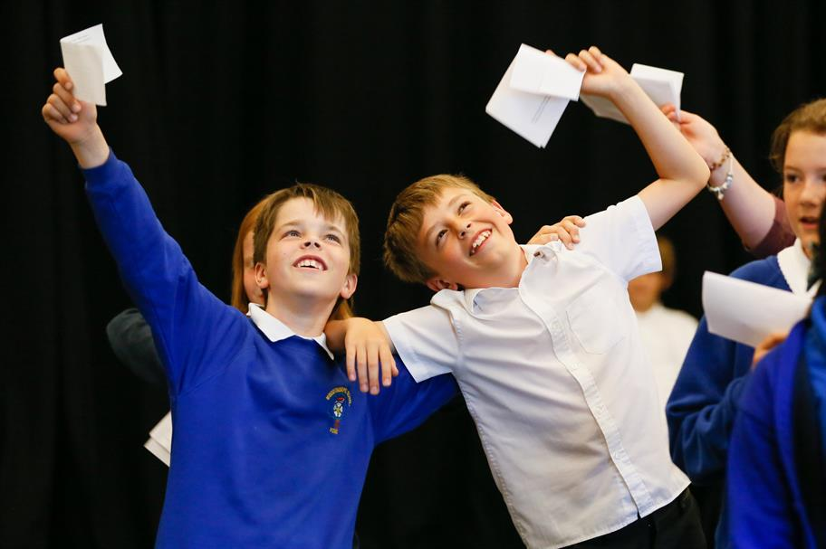 Two boys in school uniform holding pieces of paper and waving their arms in the air looking happy