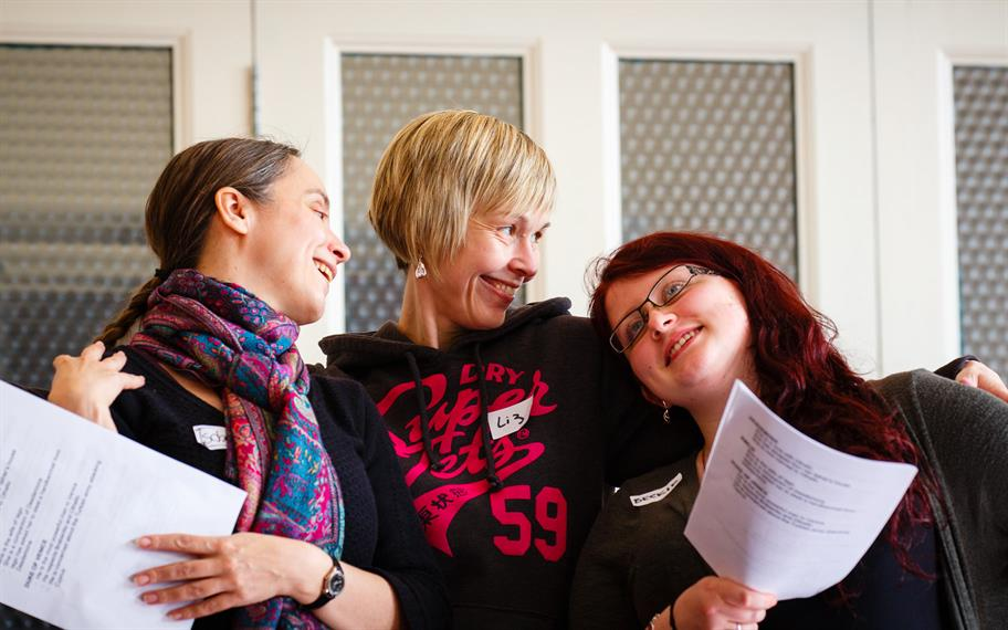 Three women, smiling. The one in the middle has her arms around the other two, who hold paper scripts.