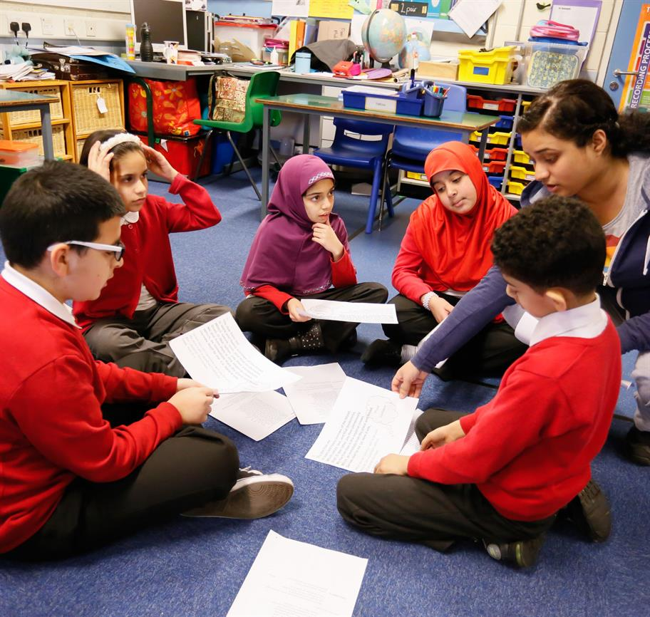 A group of children in red uniforms sit in a circle while a teacher crouching down beside them, holding a piece of paper