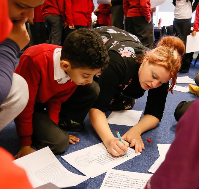 A boy wearing red school uniform and his teacher kneeling on the floor working on a sheet of paper