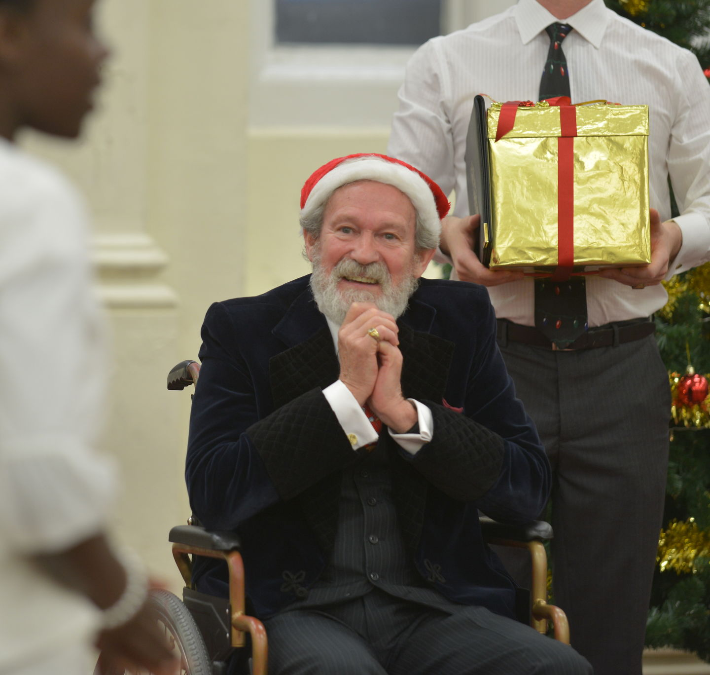 A man with a grey beard wearing a suit and a santa hat sits in a wheelchair. A man stands behind him holding a large gold-wrapped present.
