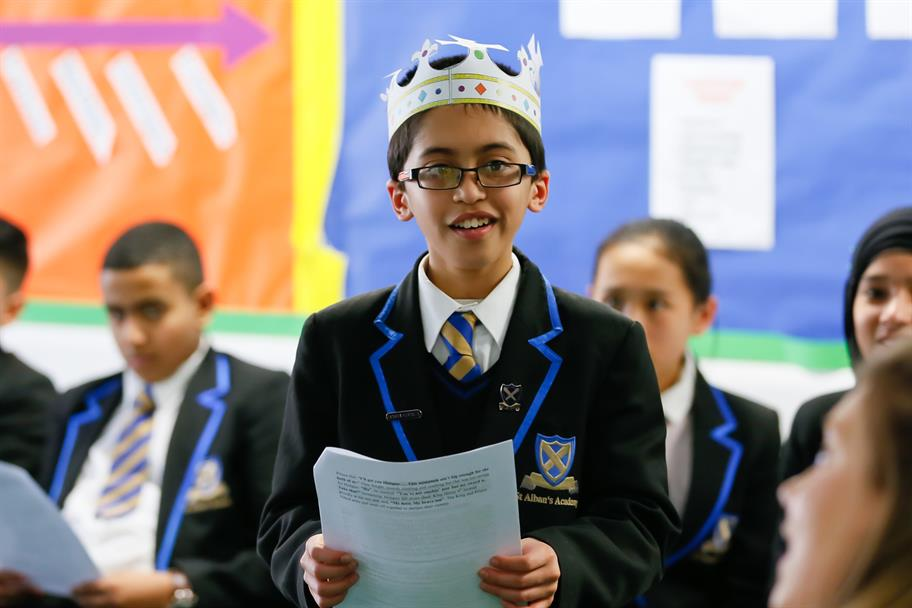 Boy in school uniform wearing a cardboard crown reading from a script