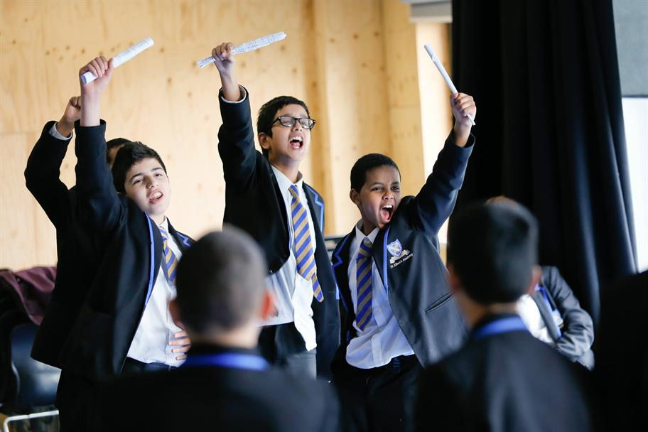 3 boys with rolled up script in hand, arm raised and shouting