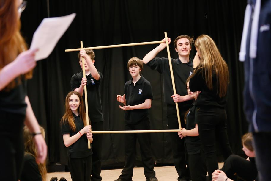 A group of young people in black hold up four sticks in the air to make a frame around another boy