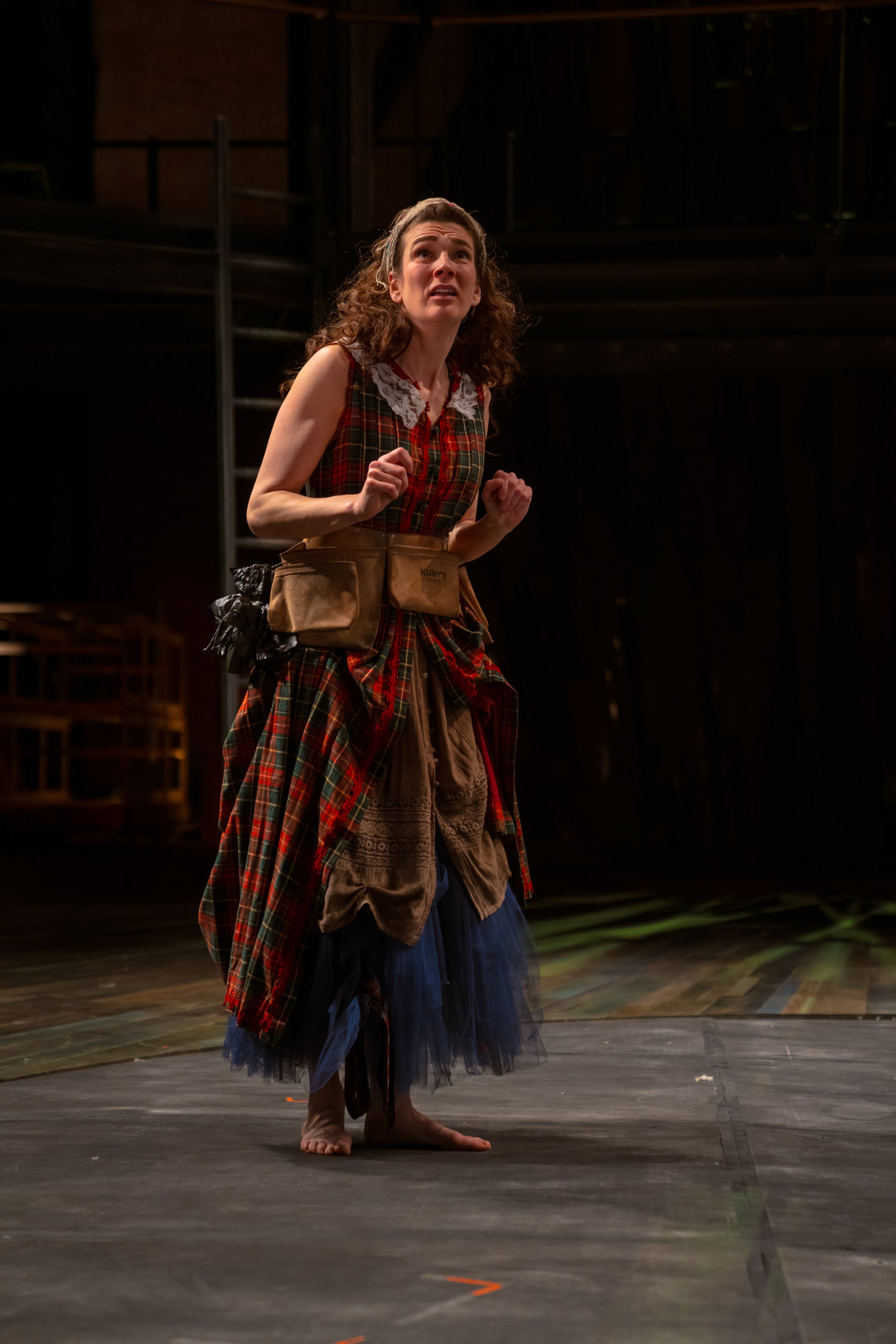 A barefoot woman in a dress made of layers of different fabrics.