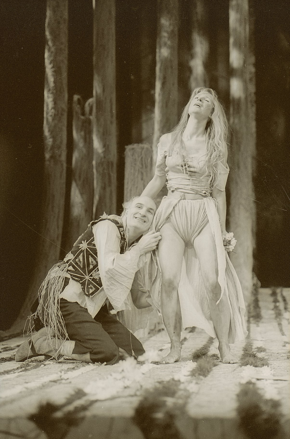 A man leans against the leg of a scantily-dressed woman.
