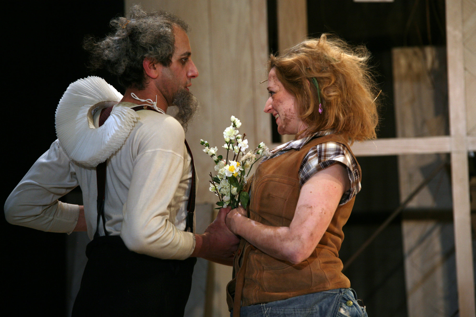 A man and woman hold flowers between them.