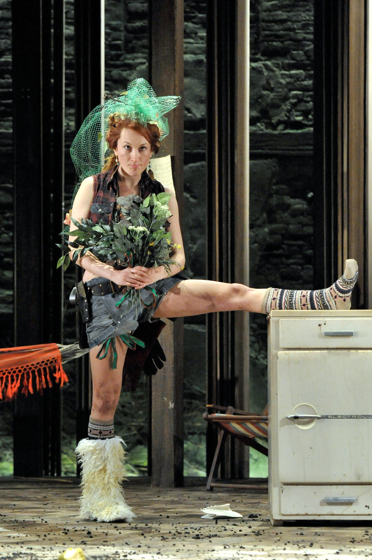 A woman holding a bouquet of leaves rests one leg on a table.