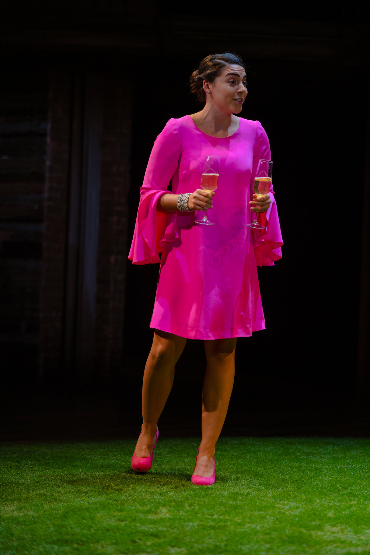 A woman in a bright pink dress holds two champagne flutes.