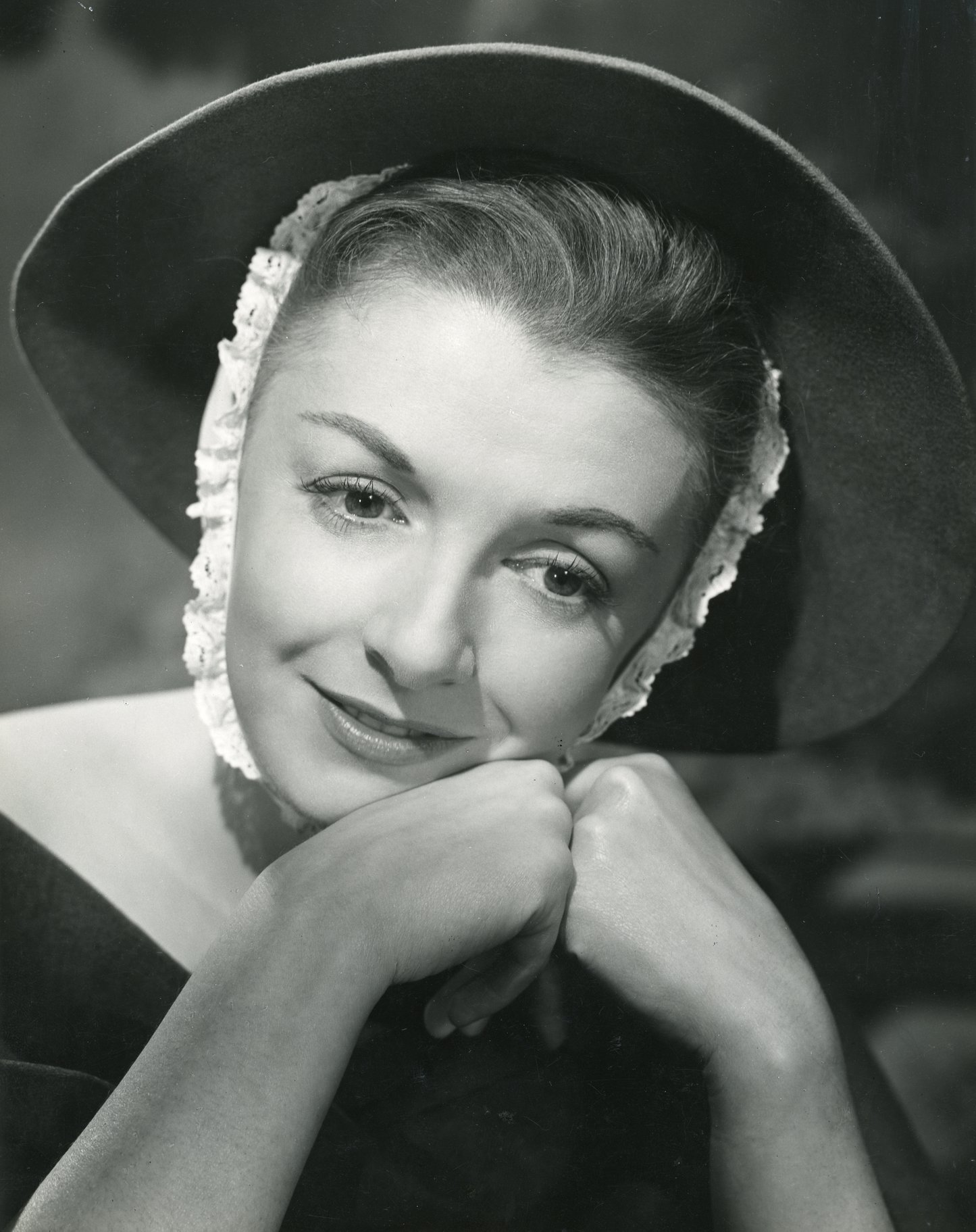 A woman in a hat rests her cheek on her hands.