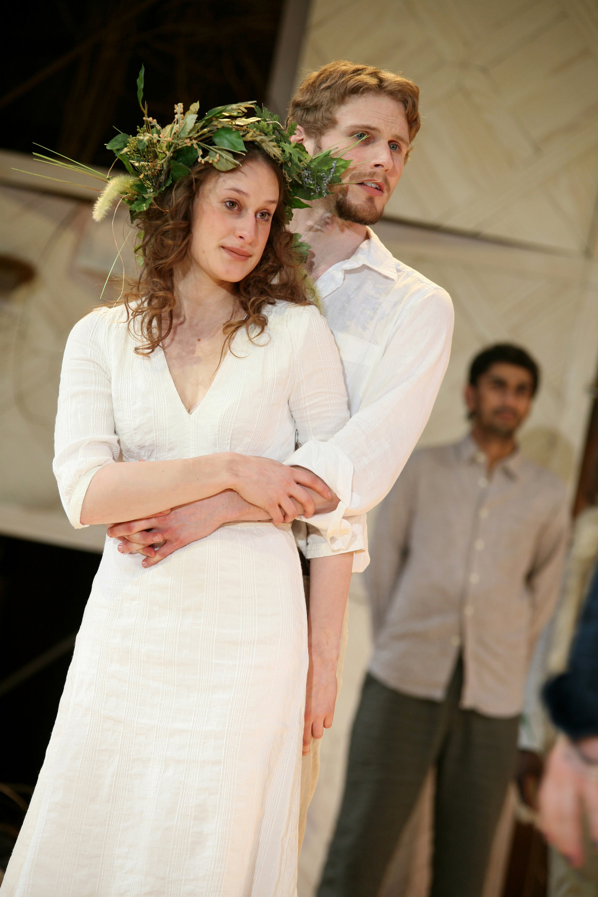 A man with his arms around a woman in white with a leafy garland.