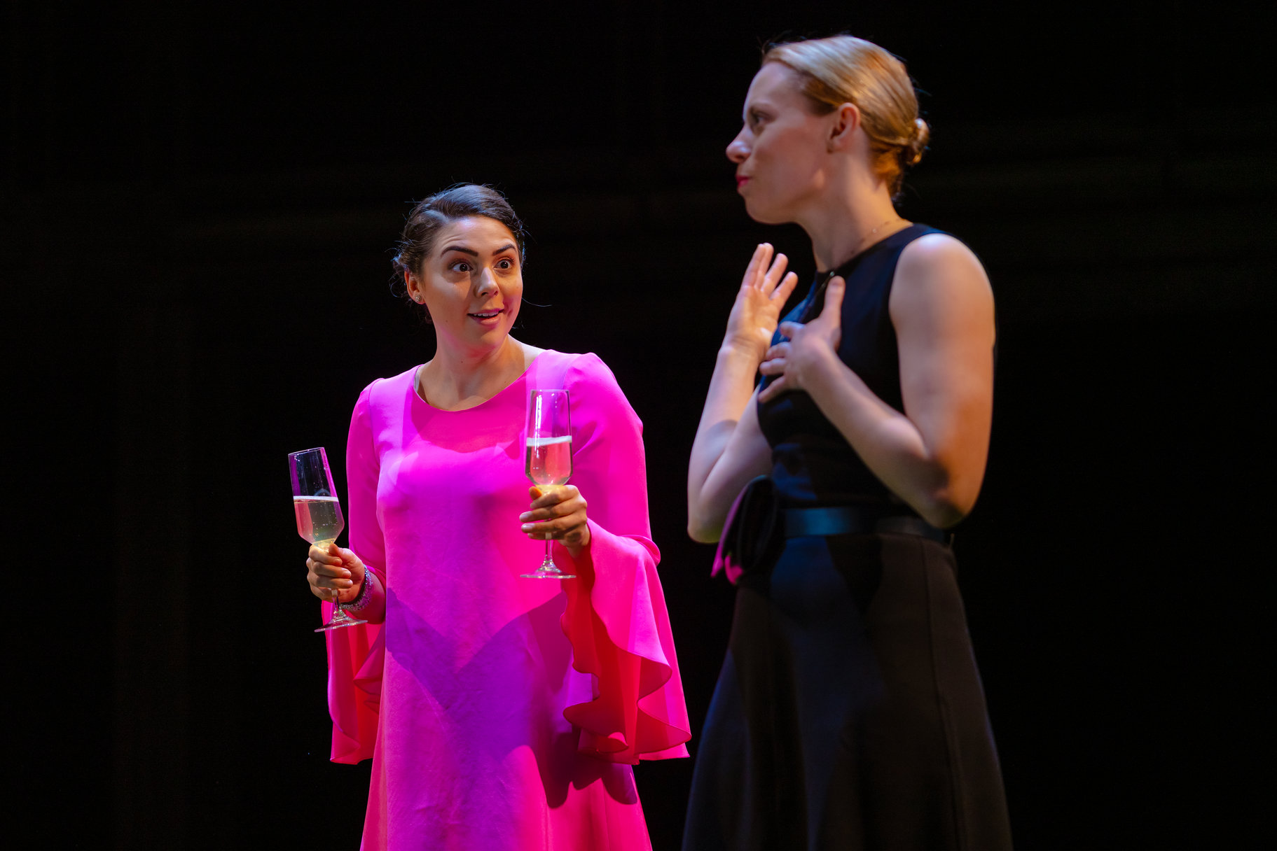 Celia and Rosalind in nice dresses, with champagne flutes.
