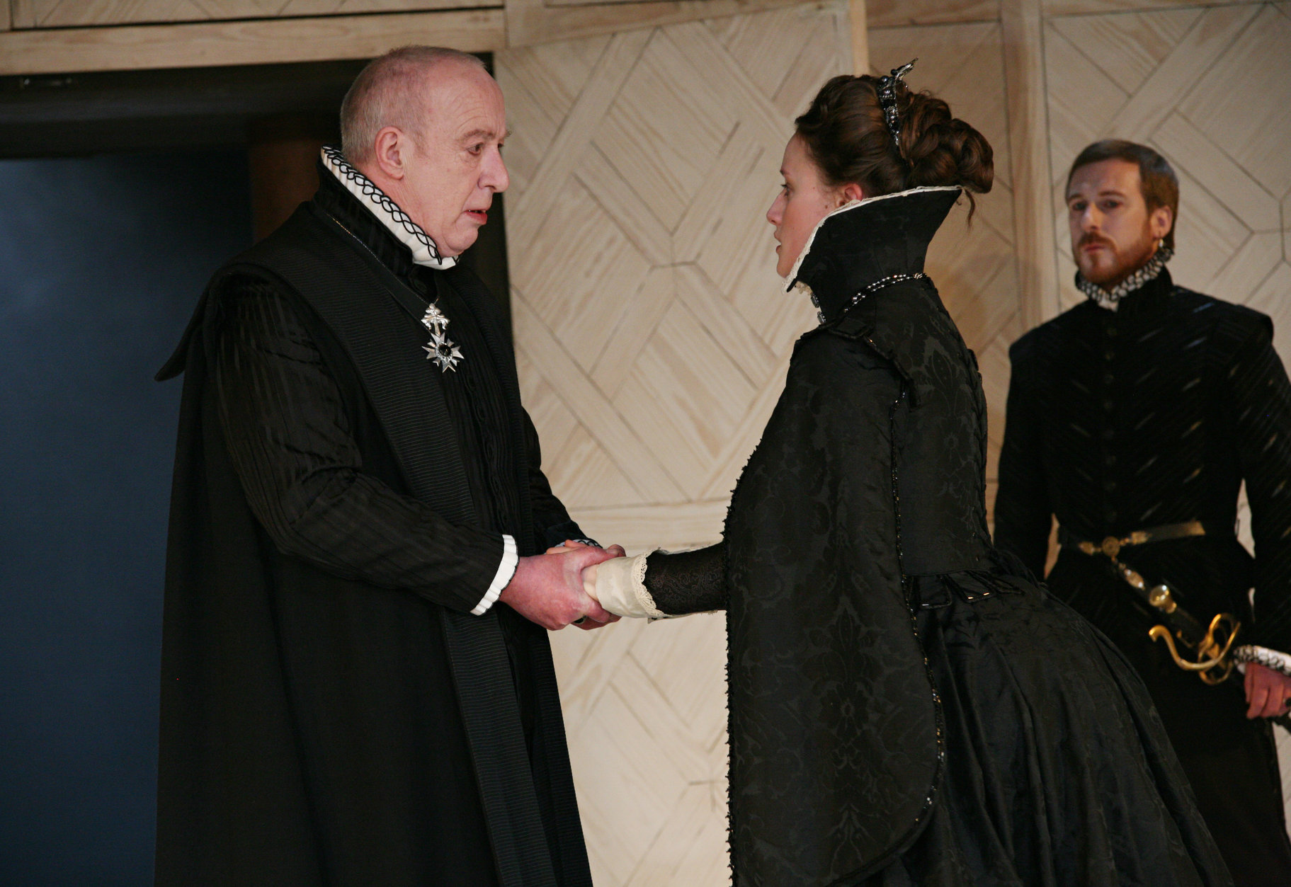 A man holds the hands of a woman in a black gown.