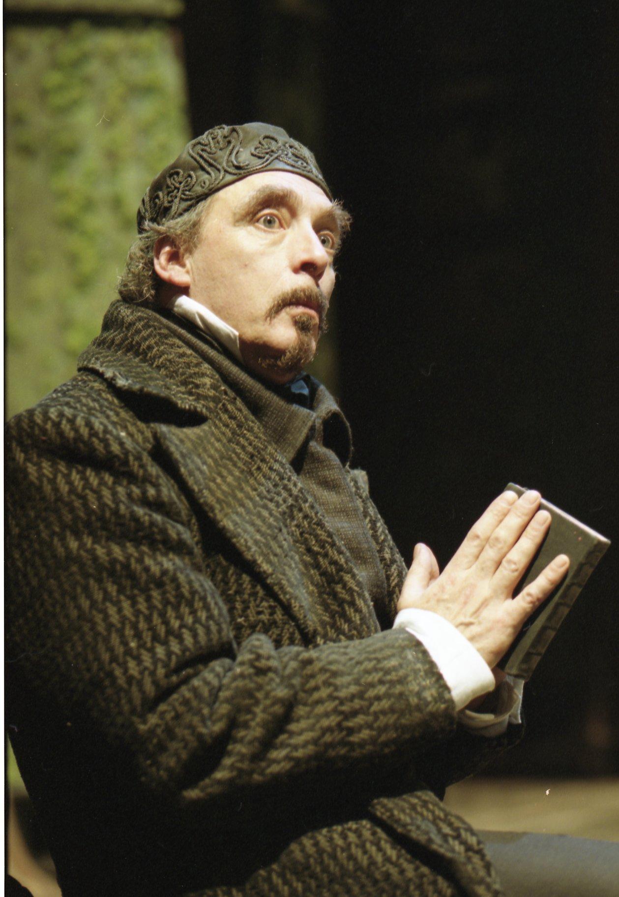 A man in a cardigan reads a book.