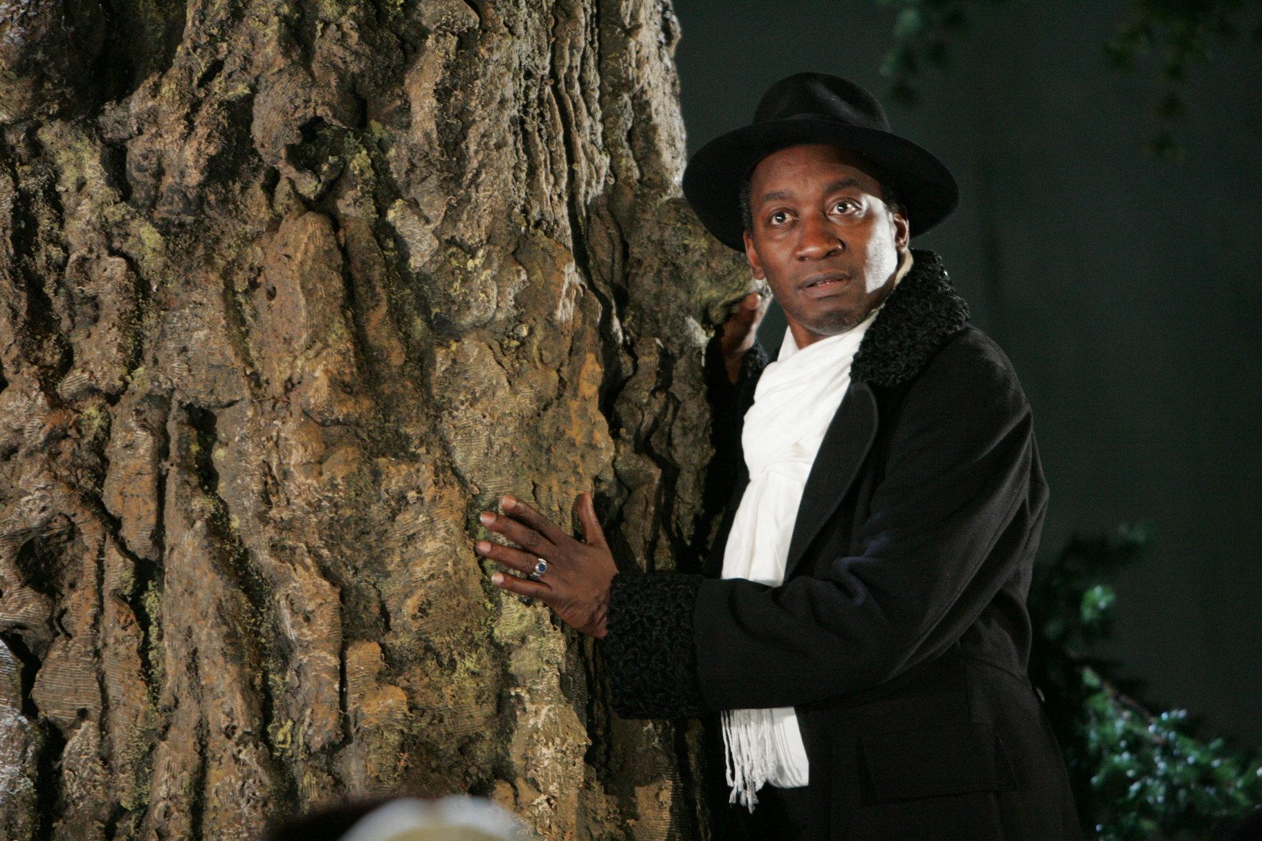 A man leans against a tree.