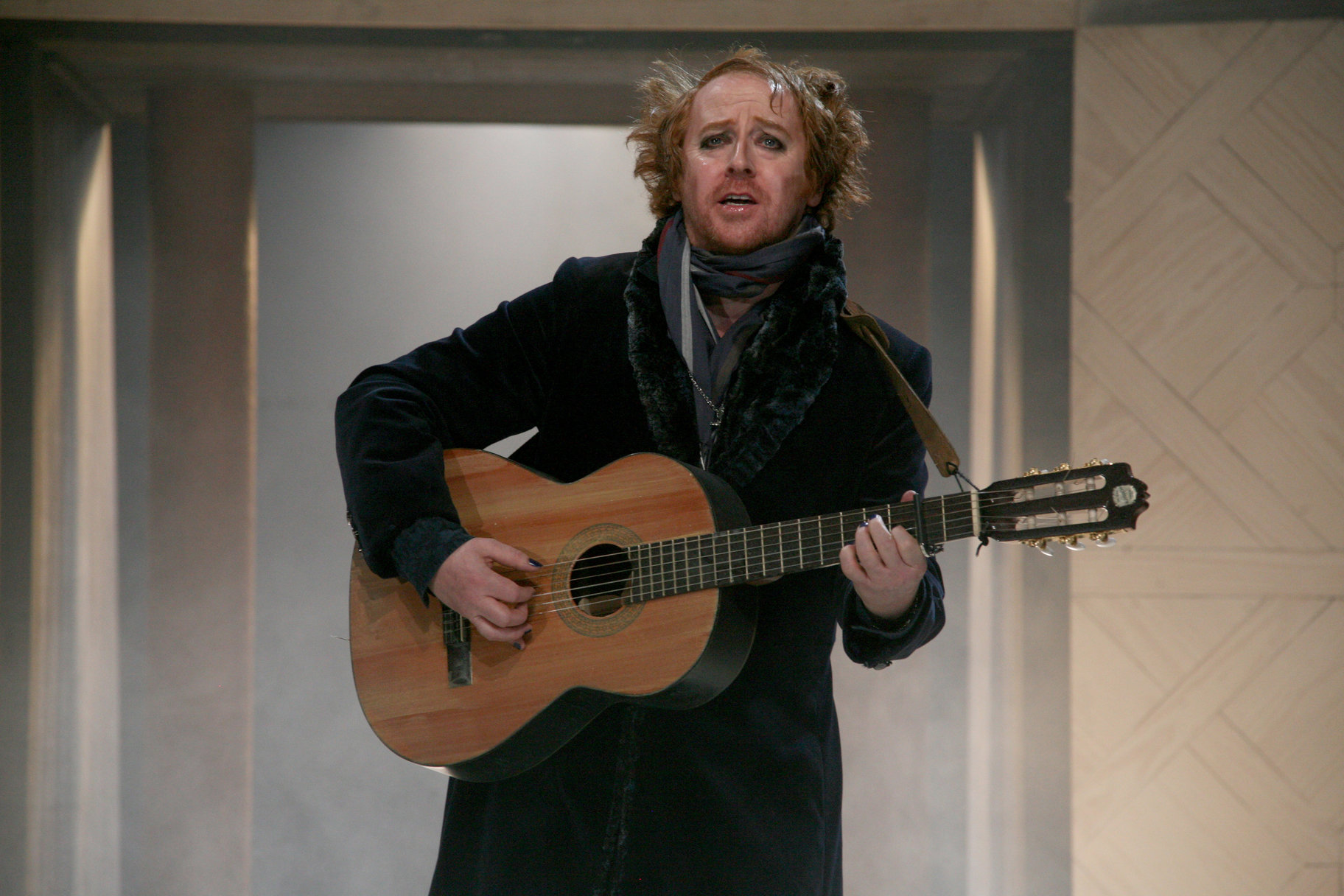 A ragged man playing the guitar.