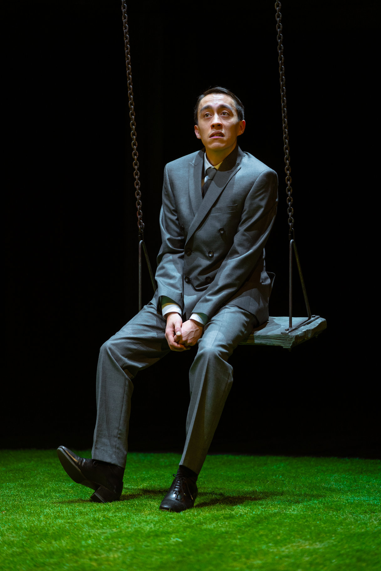 A man in a suit sits on a swing.