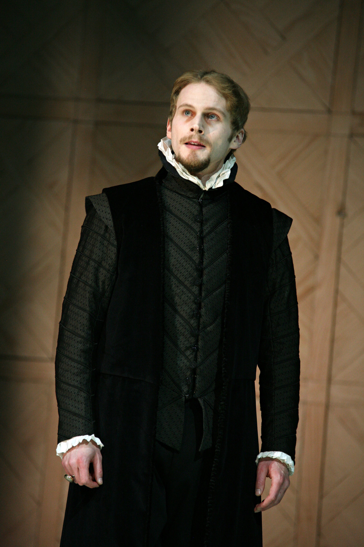 A pale man in a black suit with a small white ruff.