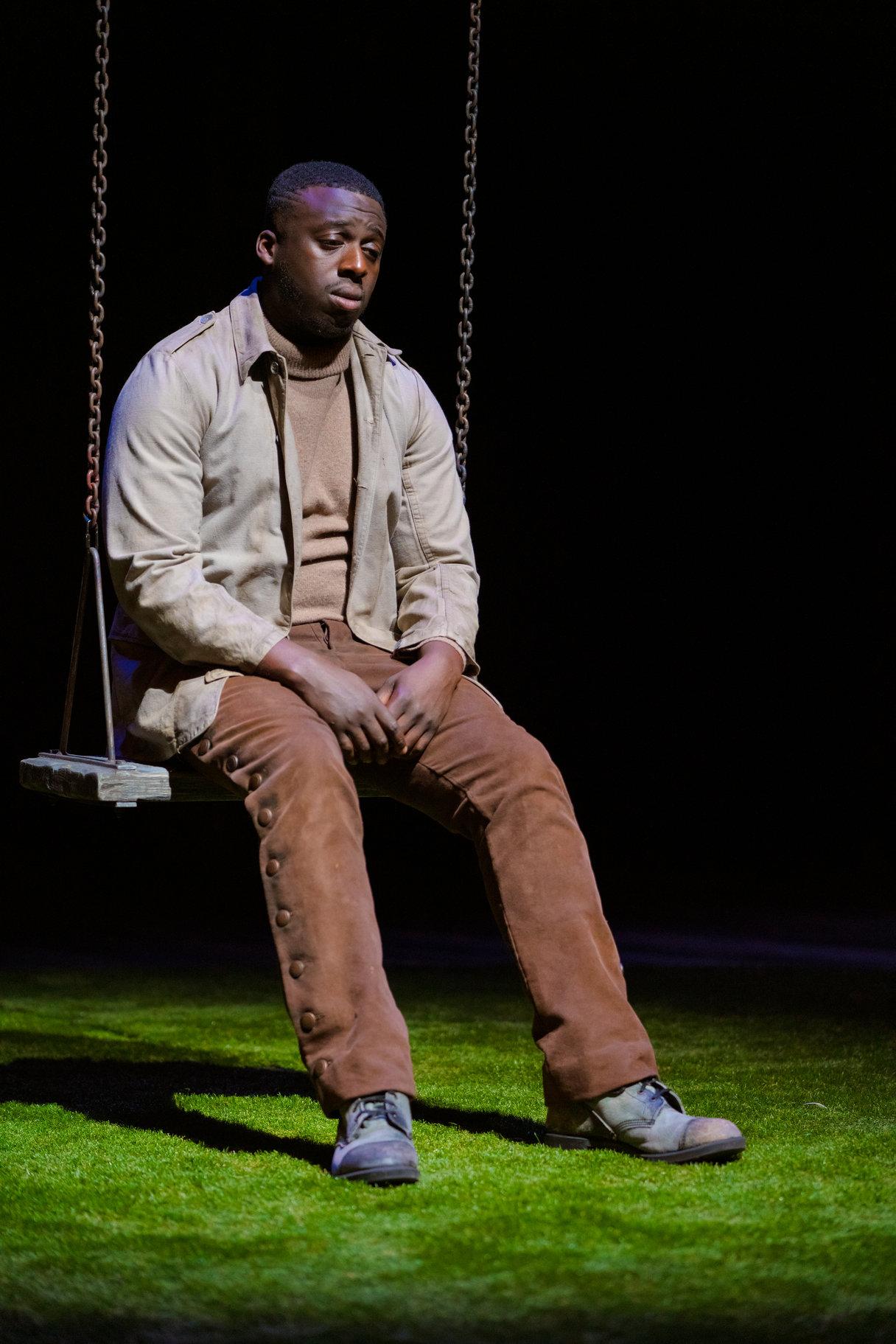 A man sits sadly on a swing.