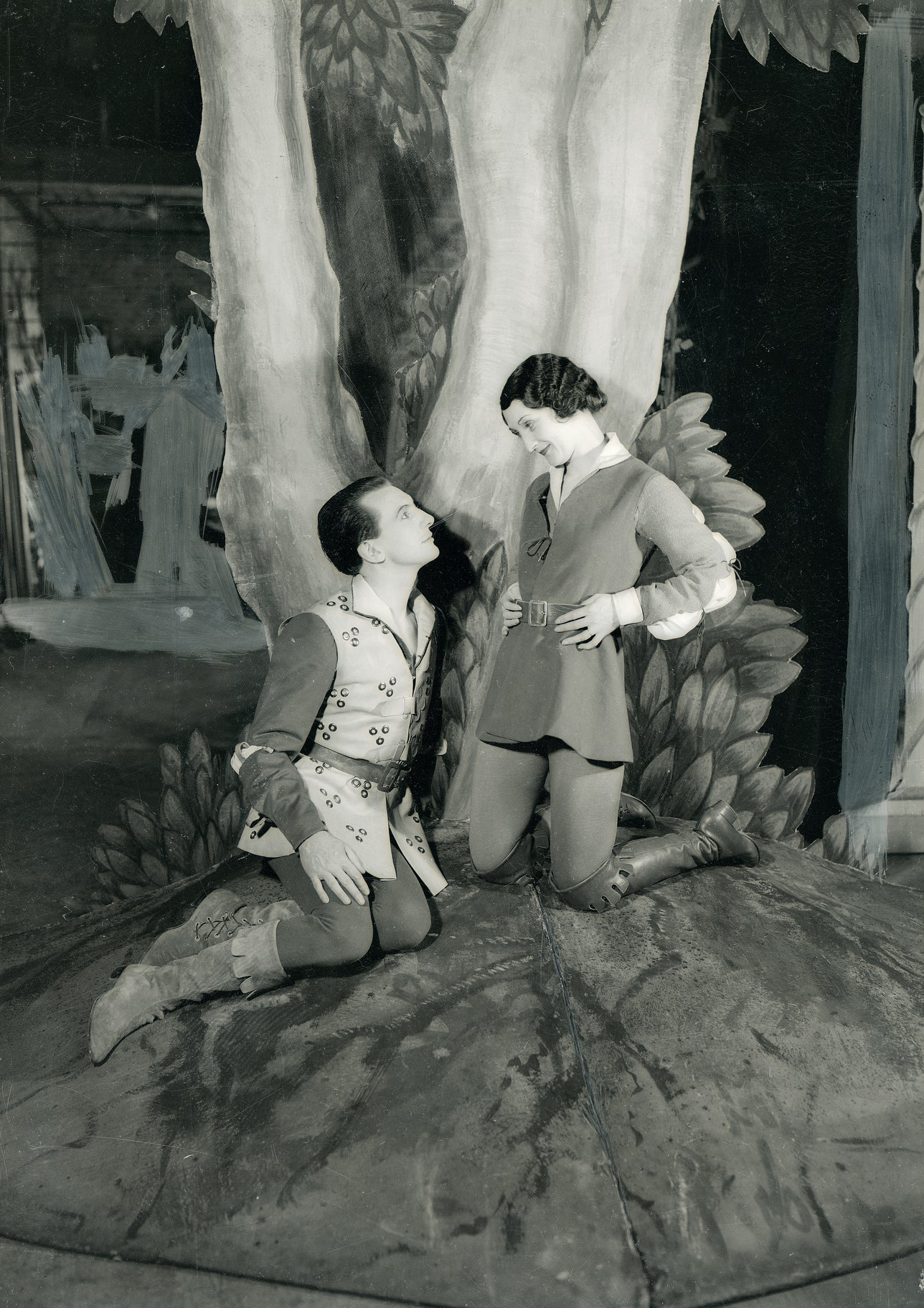 A man and woman under a cardboard tree.