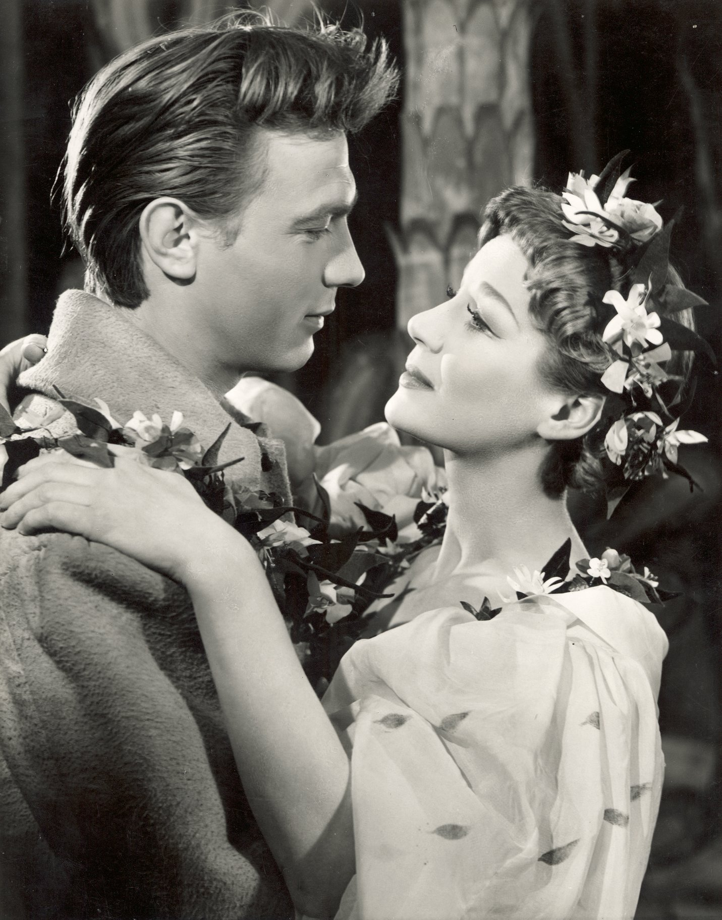 A man and woman embrace, covered with flowers.