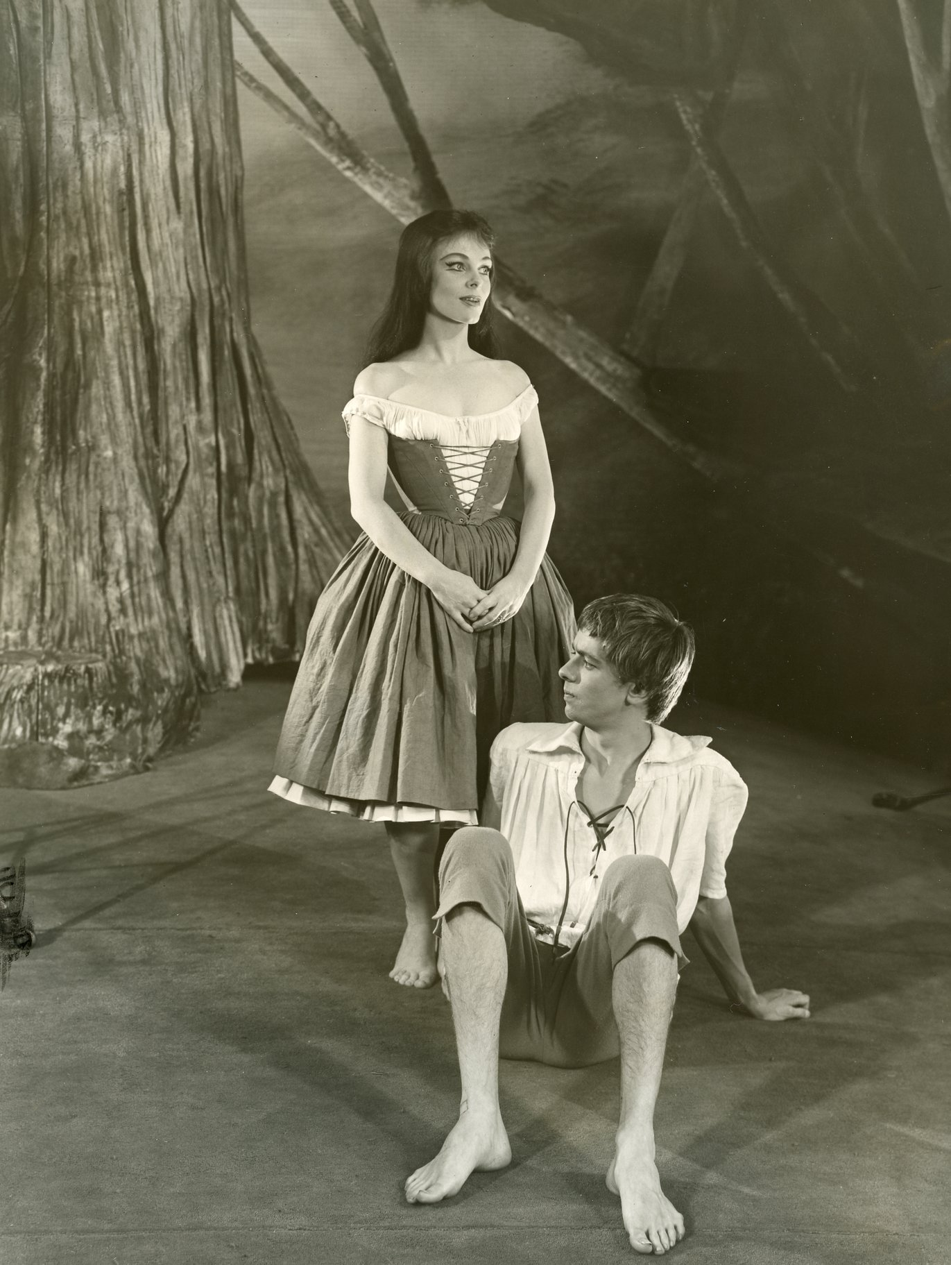 A woman stands over a man in the forest.