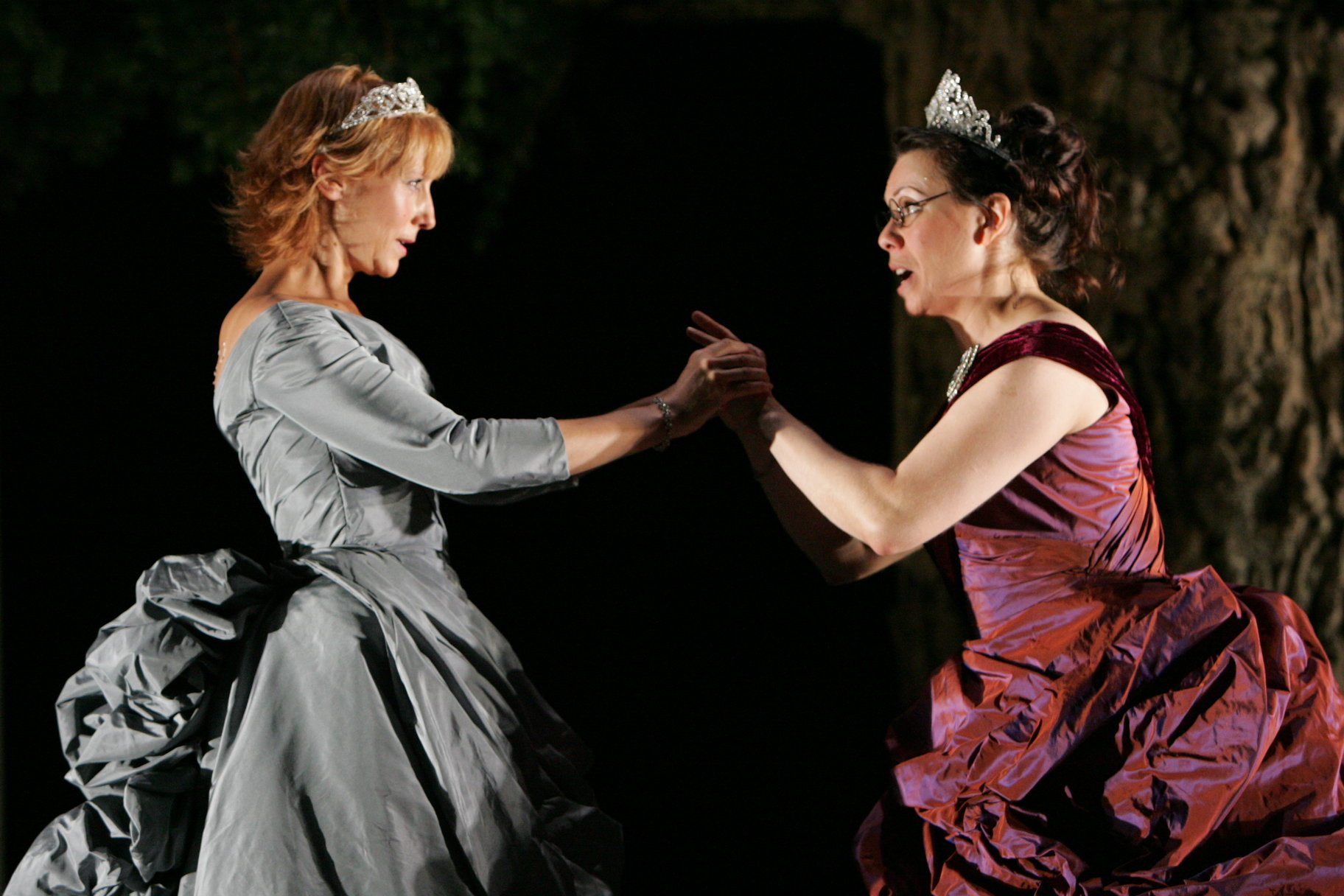 Rosalind and Celia hold hands.
