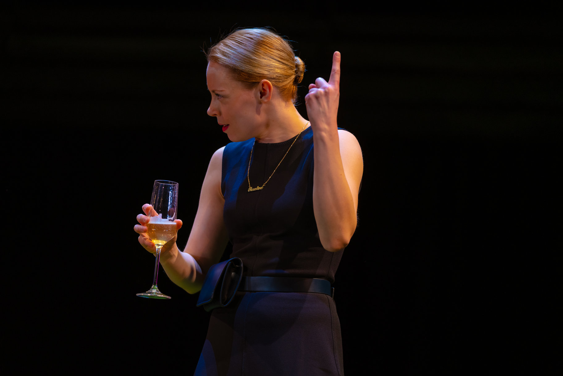 A woman in a black dress drinking champagne.
