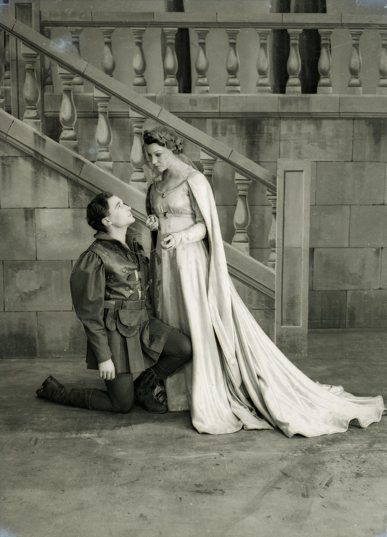 A man kneels at the feet of a woman in a long white dress.