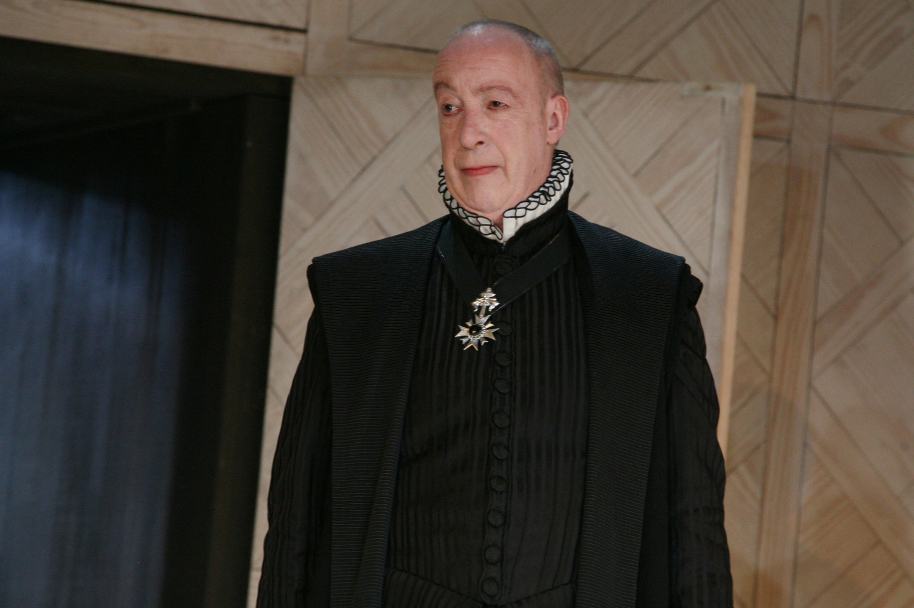 Duke Frederick in an austere black outfit with a small white ruff.
