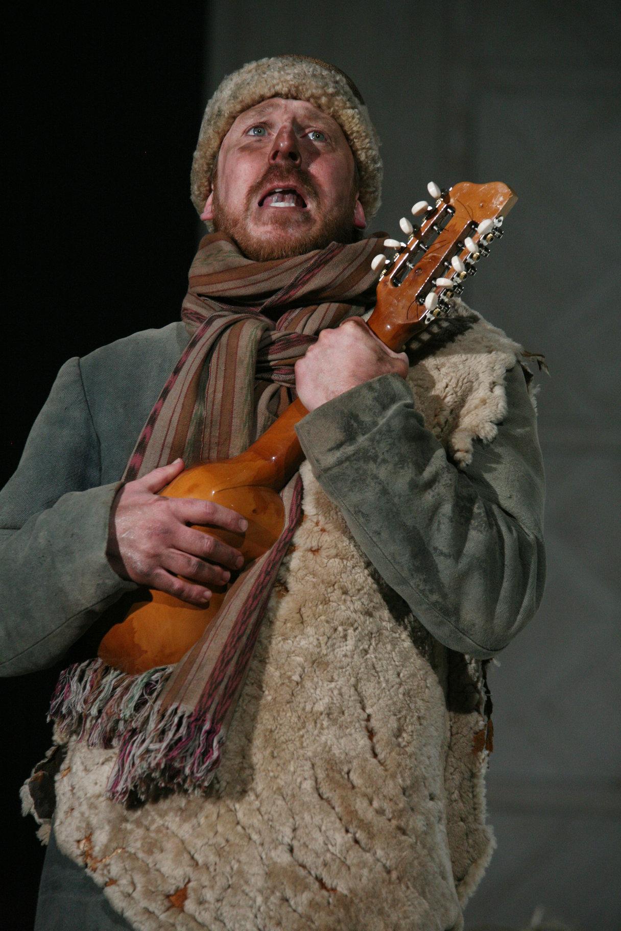 A scruffy man with a ukulele.
