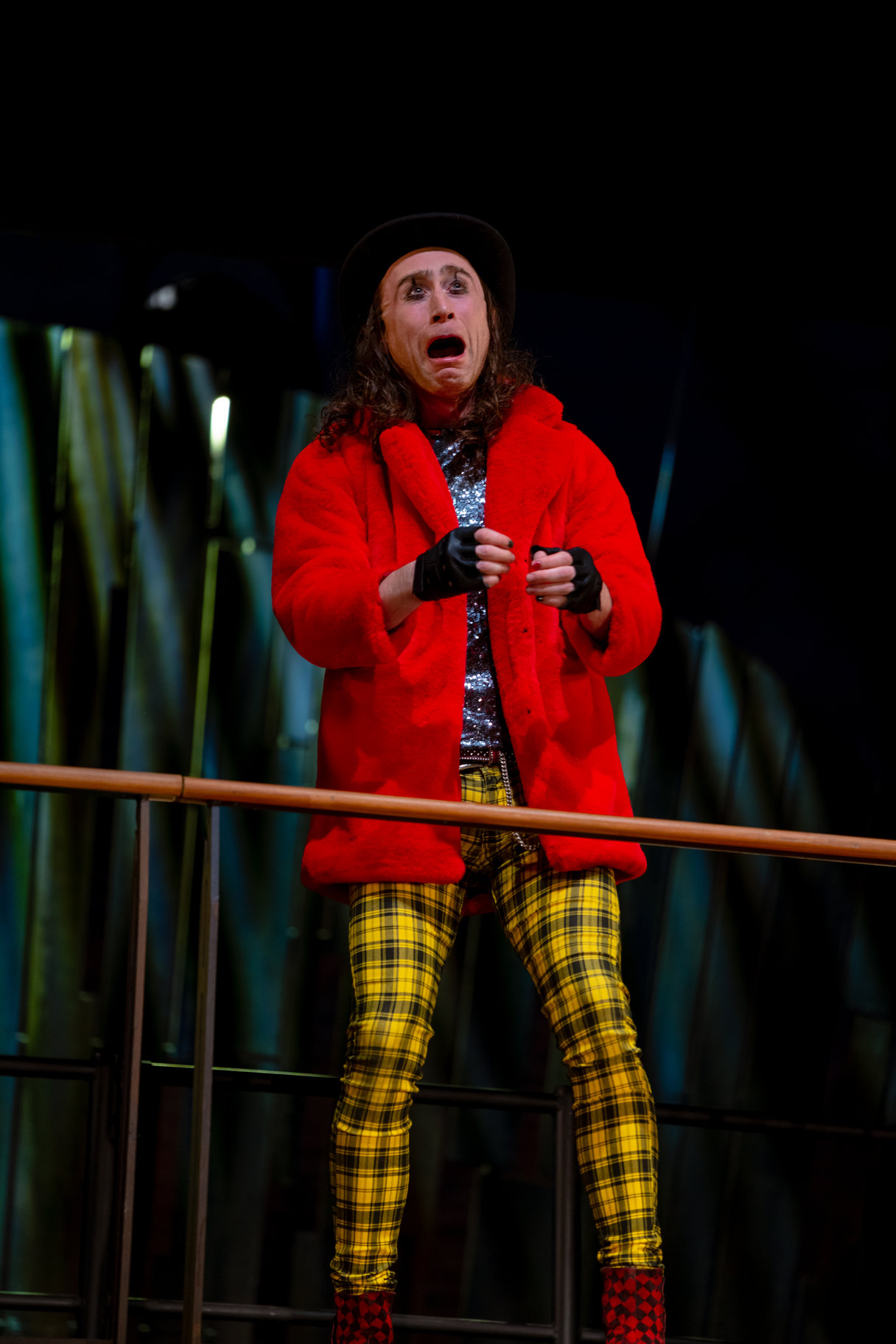 A man in a red coat and yellow checked trousers.