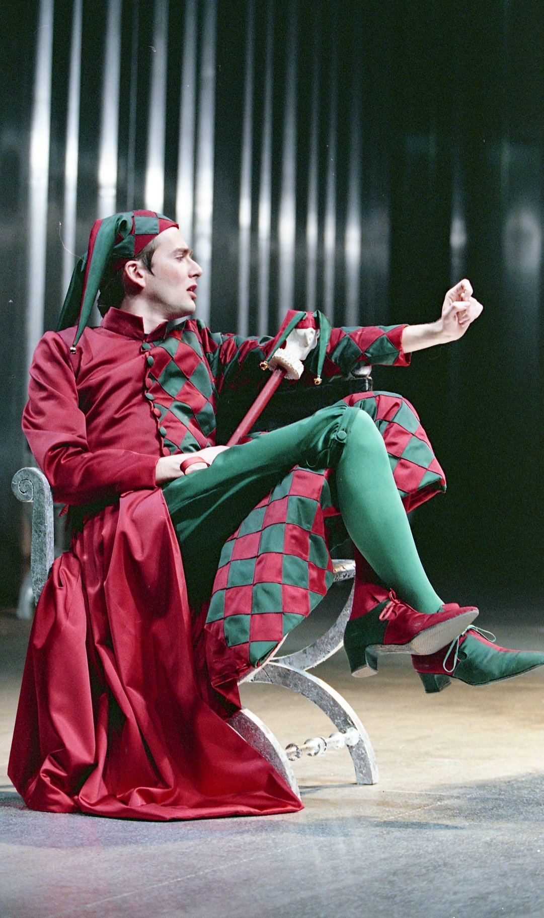A man in a red and green jester's outfit.