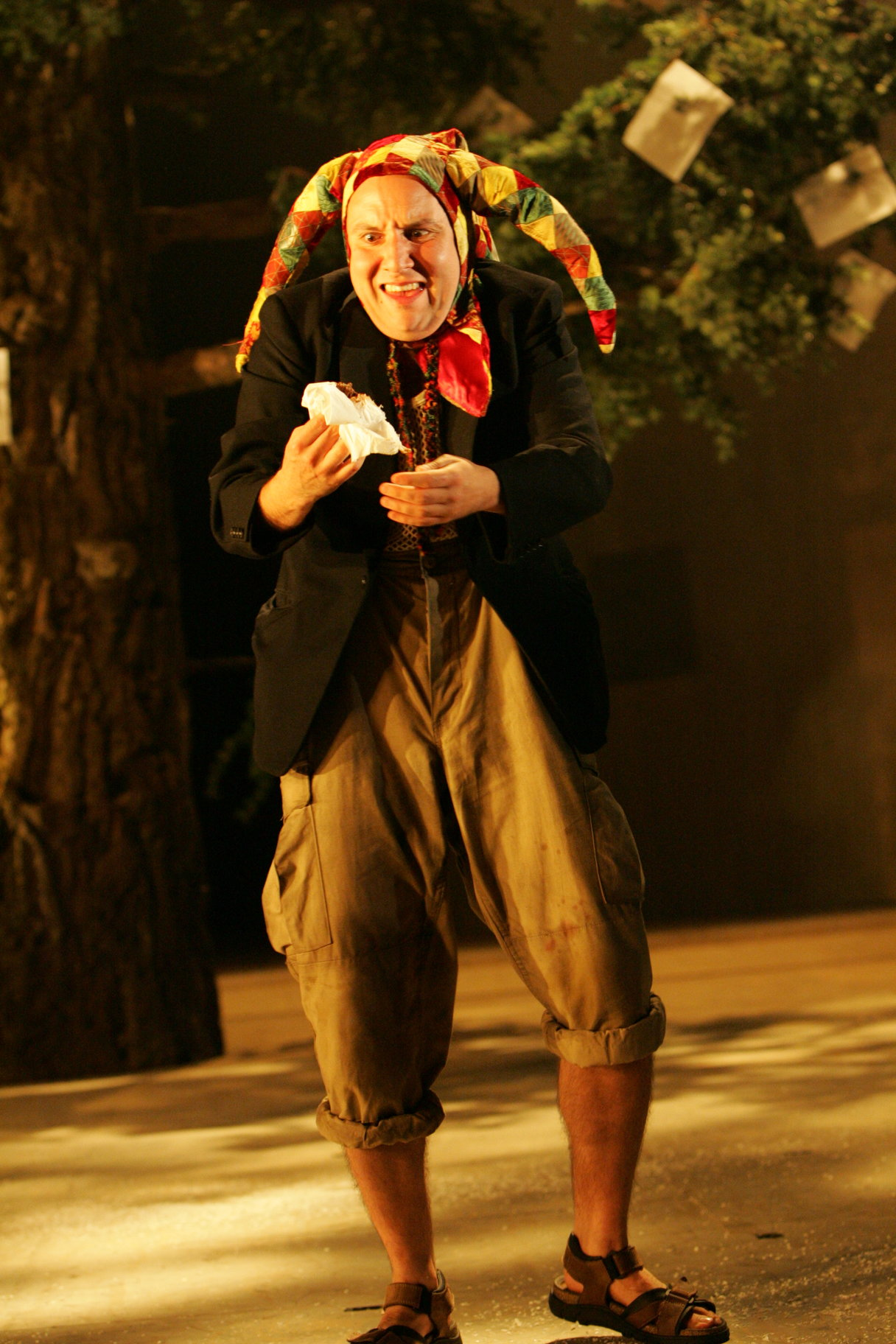 A man in short trousers and a jester's hat.